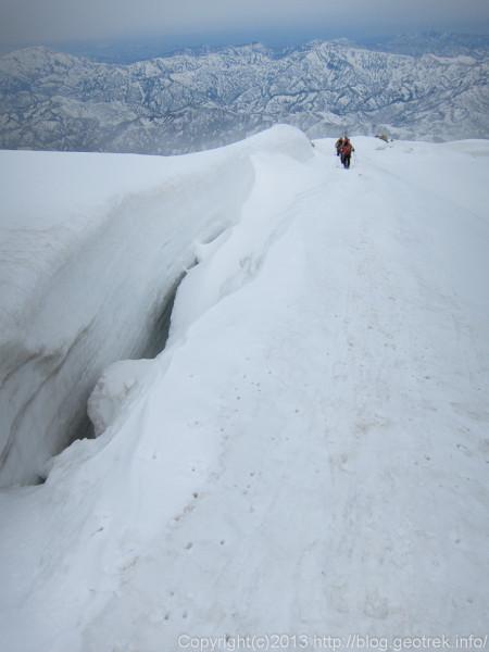 雪割れのふちを慎重に下る